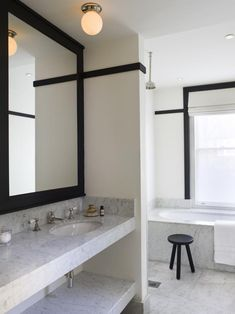 White bathroom with black trim. black stool, cararra marble counters | Remodelista
