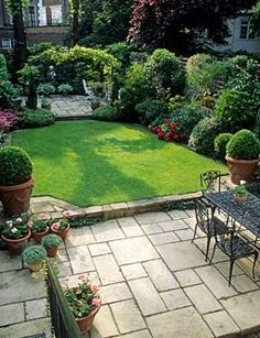 Small formal town garden with paved patio, dining table and chairs, lawn, containers, borders and arch dividing separate patio at far end of garden – London