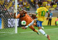 Brazil's forward Neymar (R) tries to score past Uruguay's goalkeeper Fernando Muslera during their FIFA Confederations Cup Brazil 2013 semifinal football match, at the Mineirao Stadium in Belo Horizonte on June 26, 2013. CHRISTOPHE SIMON/AFP/Getty Images