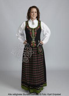 Sort Marie Aaen i toskaft med rutete forkle og brodert skjorte.