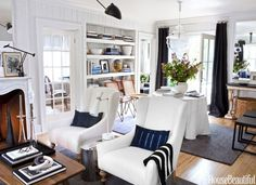 Indigo accents create a colorful thread that runs through this Ann Arbor colonial, unifying the spaces. Pillows in Archive New York's metallic stripe and D. Bryant Archie's Kampala. Chrome Oval side table from Flair. Neverending Glory Palais Garnier glass pendant by Lasvit.
