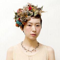 全体をしっかりUピンパーマで形をつけた後に耳上あたりからボリュームを抑えながら花とヴェールで覆いながらピンで留めていく。ボリュームあるスタイル。