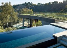"""Architecture studio Walker Workshop claims to have """"taken a hillside apart and put it back together"""" to create the subterranean base of this house in Southern California, which is topped by glass-walled living spaces and an infinity pool."""
