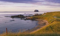 The 13th green of the east links of the Glen Golf Club at North Berwick, with the Bass Rock visible on the horizon, East Lothian, Scotland.