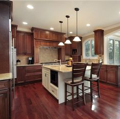 A deep rich looking kitchen design. Floor matches cabinet, but is offset with a white island.