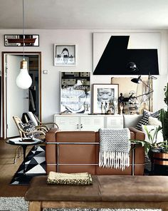 Living room with white, brown leather and black. And the art and posters on top.