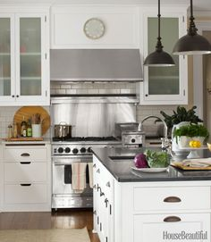Dark-bronze hardware and lighting fixtures add patina to the gleaming white kitchen. Boston pendant lights from Visual Comfort.   - HouseBeautiful.com