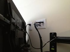 """47"""" LCD TV installed on Articulating wall mount bracket with power outlet and Custom wall plate behind the TV."""