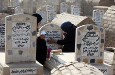 Iraqi women visit the grave of a loved one at a cemetery in the capital Baghdad during the first day of the Muslim Eid al-Adha holiday