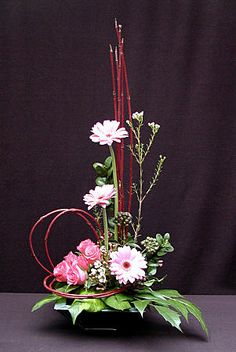 Triangular arrangement with roses, germinis and dogwood.