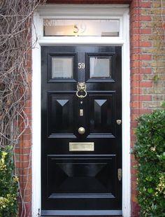 Statement lion's head door knocker on this classic black Victorian front door.