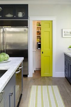 yellow pocket door to pantry. Source: James R. Salomon Photography  Jeanne Rapone - Beautiful blue & yellow kitchen with yellow pocket door leading to walk-in pantry, Dash & Albert Birmingham Citrus Woven Cotton Rug Runner, glossy blue kitchen cabinets & kitchen island with marble countertops and side by side dishwashers.