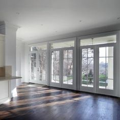 Replace four windows in sunroom with two sets of white French doors leading out to patio.