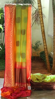 LIME GREEN BENARES SILK WITH WOVEN GOLD ZARI BHUTTAS ALL OVER. THE INTRICATELY WOVEN PINK, ORANGE AND GOLD BORDER ENDS IN A SIMPLE PALLU