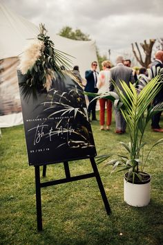 Black and White Wedding Sign with Foliage and Pampas Grass Decor | By Harry Michael Photography | Marquee Wedding | Off The Shoulder Wedding Dress | Lakeside Wedding | Neon Wedding Sign | Doughnut Wall | Donut Wall | Bridal Jacket | White Wedding Flowers | Outdoor Wedding | Wedding Decor Rustic Wedding Signs, Marquee Wedding, Wedding Welcome Signs, Wedding Signage, Lakeside Wedding, White Wedding Flowers, Wedding Styles, Wedding Ideas, Diy Wedding Decorations