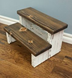 This step stool is painted cotton white with dark walnut steps, heavily distressed and finished with a polyurethane coating to protect from water