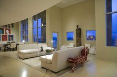 Immense open design living room sets a pair of white sofas at center, with symmetrical large scale windows surrounding. Full dining space sits below paintings at far end.