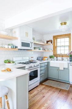 Grey, white and wood modern kitchen with open shelving and wood trim plus brass accents for a warm, casual look