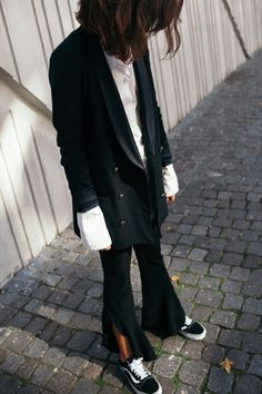 Black blazer, white button-down with oversized sleeves, flare trousers with side slits, and Vans sneakers.
