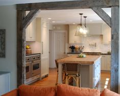 Love the use of rustic wood finised beams into the kitchen entry.