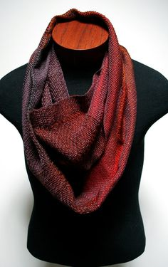 Handwoven infinity scarf with various red and orange hues made with tencel, wool, mohair and cotton.