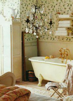 shabby chic bathroom with a freestanding tub, fun wallpaper, and ...