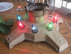 1930s cast iron christmas tree stand with electric lights,.