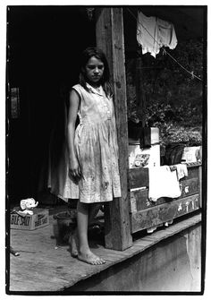 Young girl standing on a porch leaning against a support beam.. From Duke Digital Collections. Collection: William Gedney Photographs and Writings.