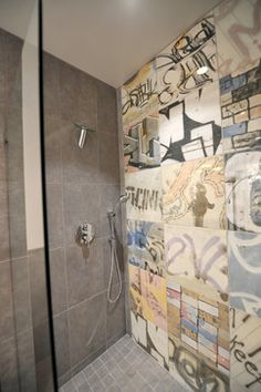 A walk in shower with graffiti tile floor to ceiling wall. Case Design Remodeling: Birmingham, AL