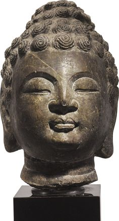 A GRAY LIMESTONE HEAD OF BUDDHA TANG DYNASTY