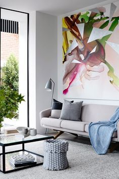 The Crisp Street Apartment was designed by Mim Design and the living room's neutral, modern decor is topped off with a beautiful, abstract painting in both bold and muted colors.