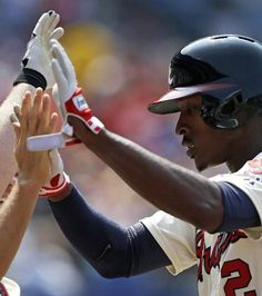 Atlanta Braves center fielder B.J.Upton celebrates at the dugout after hitting a sacrifice fly during the seventh inning of a baseball game against the Miami Marlins.