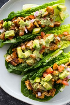 Lettuce wraps filled with spicy taco-spiced chicken, avocado, tomato, and drizzled with a zesty cilantro lime sauce. This healthy nutritious low-carb meal is a Paleo Lettuce Wraps, Lettuce Tacos, Lettuce Wrap Recipes, Chicken Lettuce Wraps, Lunch Recipes, Paleo Recipes, Mexican Food Recipes, Low Carb Recipes, Cooking Recipes