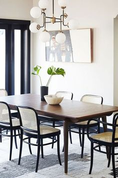 dining room with simple wood table, mid century light fixture, and wicker and wood chairs
