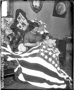 Mrs. Margaret McBride and daughters sewing an American flag while sitting on a sofa in a living room in Chicago, Illinois, c. 1917. Photograph from the Chicago Daily News. DN-0069332 #chicago #history #holidays #america #flag #july4