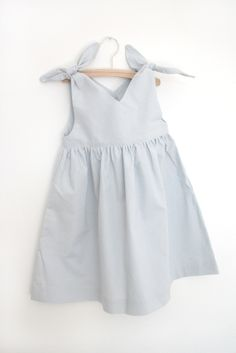 A classical girls dress shape from the 50s...We love our Rabbit Dress!Knotted on the shoulder with a teardrop detail in the back.Pale grey cotton with tiny cream dotsMade with love in Germany