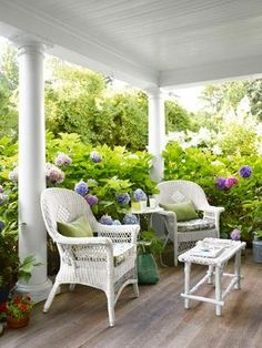 hydrangeas encroaching into a relaxing white porch set with two white wicker chairs.