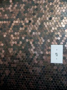 This could be considered defacement of currency, but I'd love a penny wall in my house just the same.