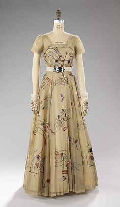 Music was the theme for Schiaparelli's fall 1939 collection, which manifested itself in music boxes on belts and hats, buttons shaped like drums, and shimmering embroidered instruments and music notes. This particular evening dress, worn by Millicent Rogers, was accessorized with a belt with a working music box as the buckle.