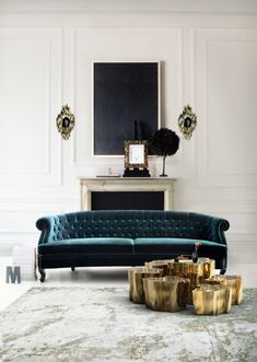Every element works beautifully in this Parisian living room... the sumptuous velvet couch, the cluster of gold side tables, the intense, graphic black artwork... all set against a classic white backdrop. Exquisite.