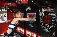 Throwing punches: The stunner focused on hitting the target while playing arcade games - featuring her name emblazoned on the front