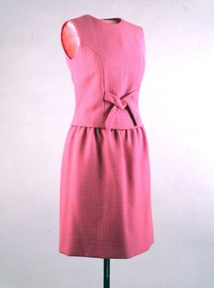 """Dress Maker: Joan Morse (fashion designer) Date(s) of Materials: 1962 Place Made: United States Medium: Wool Dimensions: 37"""" center back Description: A sleeveless rose-pink dress in basket-weave wool with an A-line skirt and a bow at the center of the waist. This dress was purchased from Joan Morse's Manhattan boutique, A La Carte. Historical Note: This dress was worn by Jacqueline Kennedy in Miami when she addressed the Cuban Brigade, survivors of the Bay of Pigs landings in Cuba."""