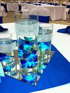 Submerged blue orchids with bling wrap trimmed vases (can top with floating candles or light with LED) Silver Centerpiece, Floating Candle Centerpieces, Royal Blue Centerpieces, Royal Blue Wedding Decorations, Wedding Ideas Blue, Turquoise Centerpieces, Blue Vases, Led Candles, Flower Centerpieces