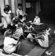 A Turkish boy (center) rents out comic books to local children to support his family in the Philippines in 1945.