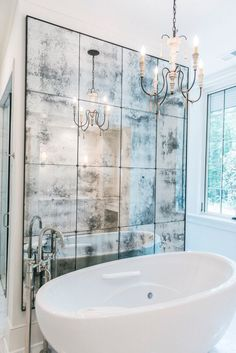 This bathroom looks gorgeous with this beautiful wall of antique mirror and the freestanding @BainUltra Essencia Oval tub. Find more info on this #bathtub here : http://www.bainultra.com/therapeutic-baths/our-collections/essencia/essencia-oval-7236