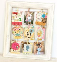 Frame with hanging cards and pictures.  Papers by Maya road