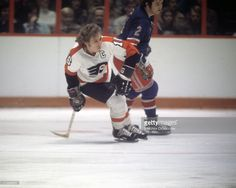 Bobby Clarke #16 of the Philadelphia Flyers and Brad Park #2 of the New York Rangers skate on the ice during an NHL game circa 1975 at the Spectrum in Philadelphia, Pennsylvania.