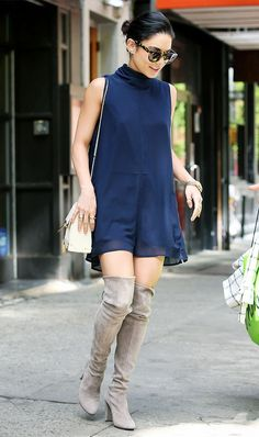 Vanessa Hudgens wears a navy blue mini dress, thigh-high suede boots, and a white shoulder bag