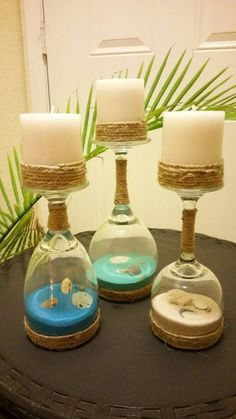 This is a set of 3 Wine glasses turned into Candle holders. Inside Wine glasses are colored sand and real seashells. The color blue in pictures I am having trouble getting but I have other color options. See pictures. I have light blue, dark blue, medium blue, coral, natural color, black, and turquoise. If wish for a different color then send me message I will see what I can do. The glasses have twine wrapped around them. This set comes with candles included. The candles also have twine…