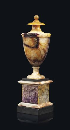 A GEORGE III BLUE JOHN SOLID URN CIRCA 1800 Of typical form with ball finial above a tapering body on a stepped square plinth bordered with alabaster and slate